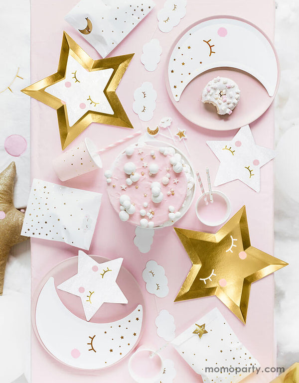 A flatlay shot of a baby pink table setup for a sweet baby shower filled with sweet Star themed party goods including die cut gold star plates, little star napkins in white, moon shaped plates in white with pink party cups and party favor bags
