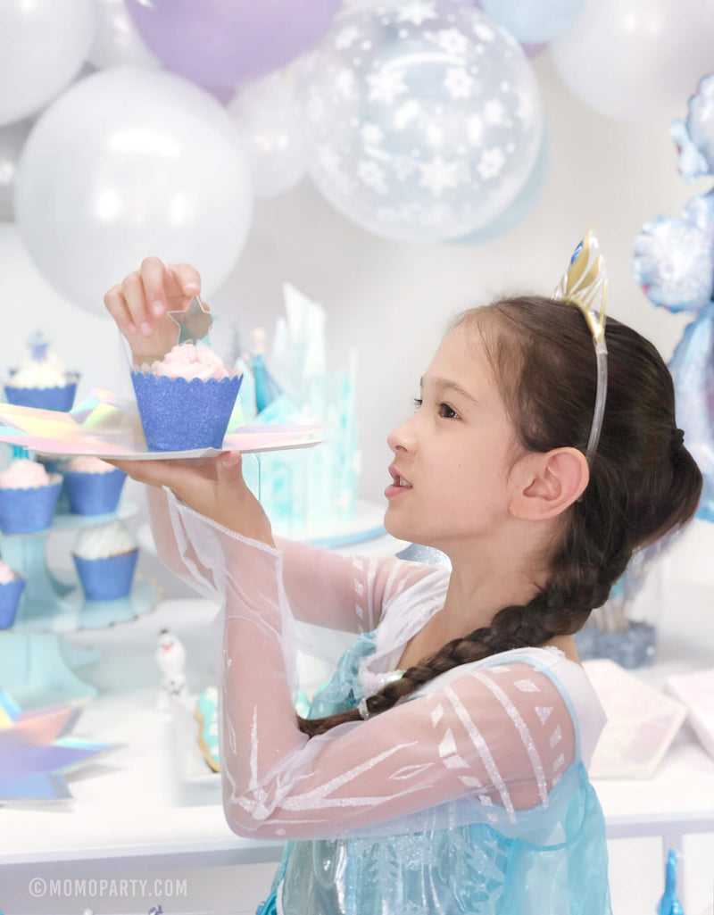 A girl wearing Elsa Princess costume holding a cupcake with Glitter Ice Blue Cupcake Wrapper on a star plate in her Frozen themed birthday party