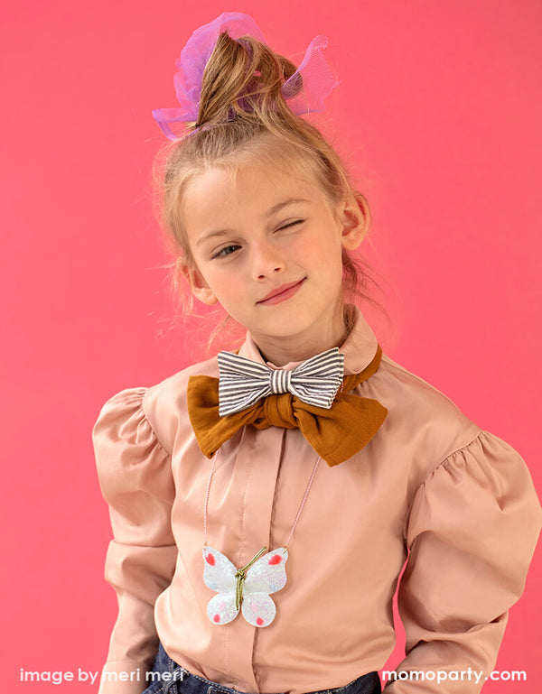 a cute girl wearing a fun modern wardrobe with Balloon sleeves tops and double ties, a pom pom sleeve shirt. a Meri Meri Glitter Butterfly Necklace. This cute necklace is beautifully crafted from iridescent glitter fabric with 'gem' embellishments and has a stylish rose gold enamel bead chain.