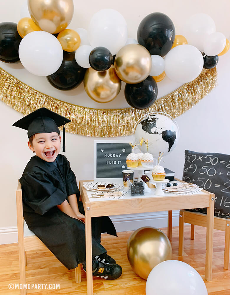 "happy little kindergarten graduator wearing a black graduation gown celebrate at home with a modern graduation party look, which has black, gold and silver balloon garland, Gold Tinsel Fringe Garland on the wall, black stripe plates, napkins, Assorted Gold Dipped Cups, b&w globe, letter board with ""hooray i did it"" sign, cupcakes, black gum balls on a kid desk"