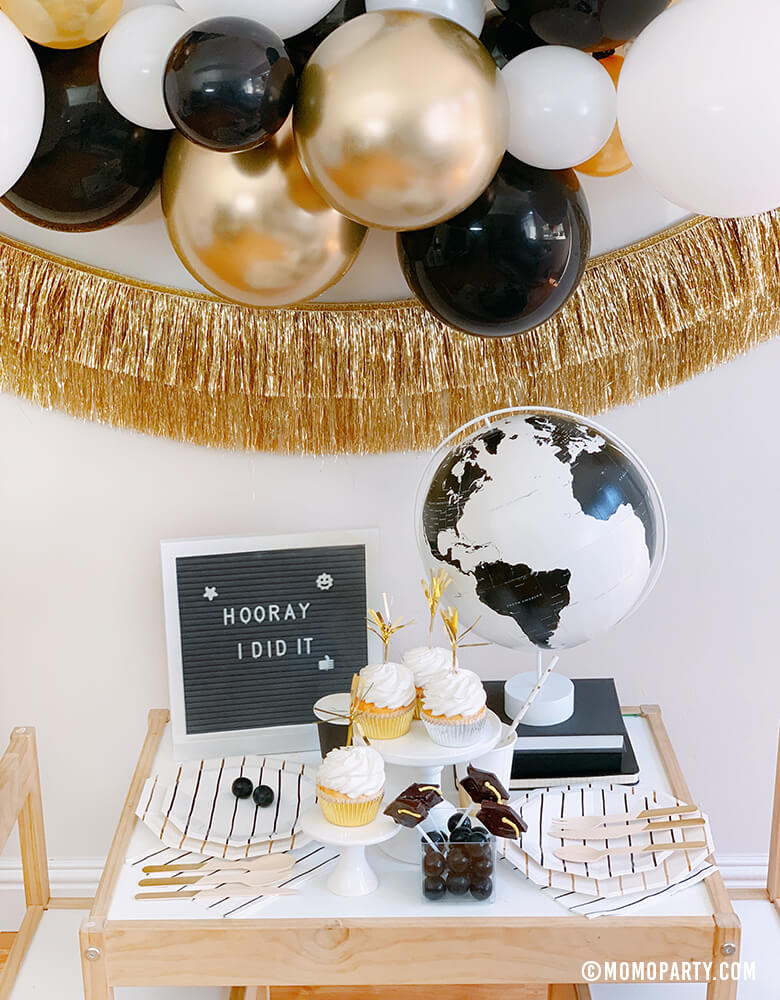 "front look of a modern graduation party at home with black, gold and silver balloon garland, Black Graduation Cap Foil Balloon, Gold Tinsel Fringe Garland on the wall, black stripe plates, napkins, Assorted Gold Dipped Cups, b&w globe, letter board with ""hooray i did it"" sign, cupcakes, black gum balls on a kid des"