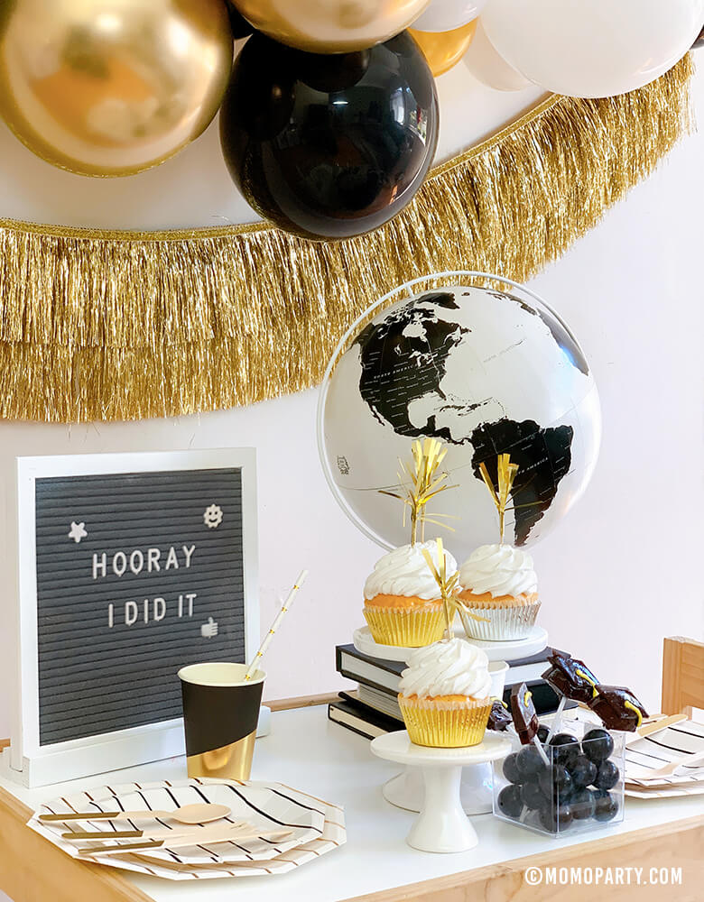 "Modern graduation party at home idea with black, gold and silver balloon garland, Black Graduation Cap Foil Balloon, Gold Tinsel Fringe Garland on the wall, black stripe plates, napkins, Assorted Gold Dipped Cups, b&w globe, letter board with ""hooray i did it"" sign, cupcakes, black gum balls on a kid desk"