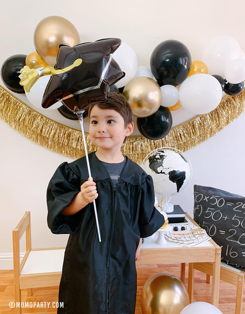 "a kindergarten boy wearing a black graduation gown, holding a Black Grad Cap Mini Foil Balloon, celebrate at home with a modern graduation party look, which has black, gold and silver balloon garland, Gold Tinsel Fringe Garland on the wall, black stripe plates, napkins, Assorted Gold Dipped Cups, b&w globe, letter board with ""hooray i did it"" sign, cupcakes, black gum balls on a kid desk"