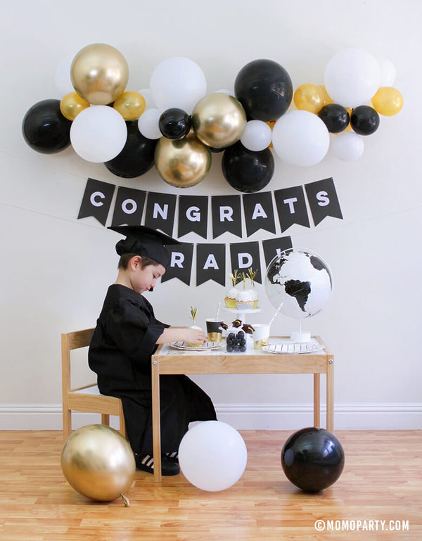 "2020 Graduation at home celebration with boy siting in from the a desert table with cupcakes, black stripe plates, graduation hat lollipop,  black and white globe, books and Black banner with ""Congrats Grad!"" sign and Balloon garland with gold, black, white as wall decoration"