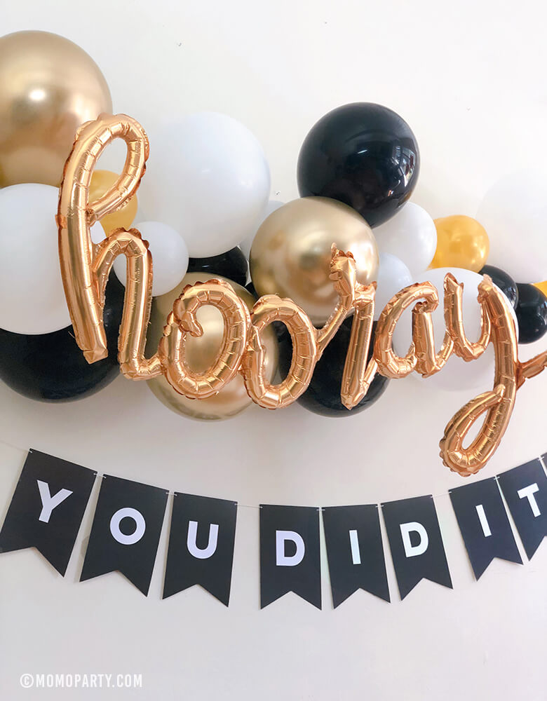 "Black, gold and white balloon garland with Hooray Gold Script Mylar Balloon, and Black customized letter banner spelled with ""you did it"" for a modern graduation celebration."