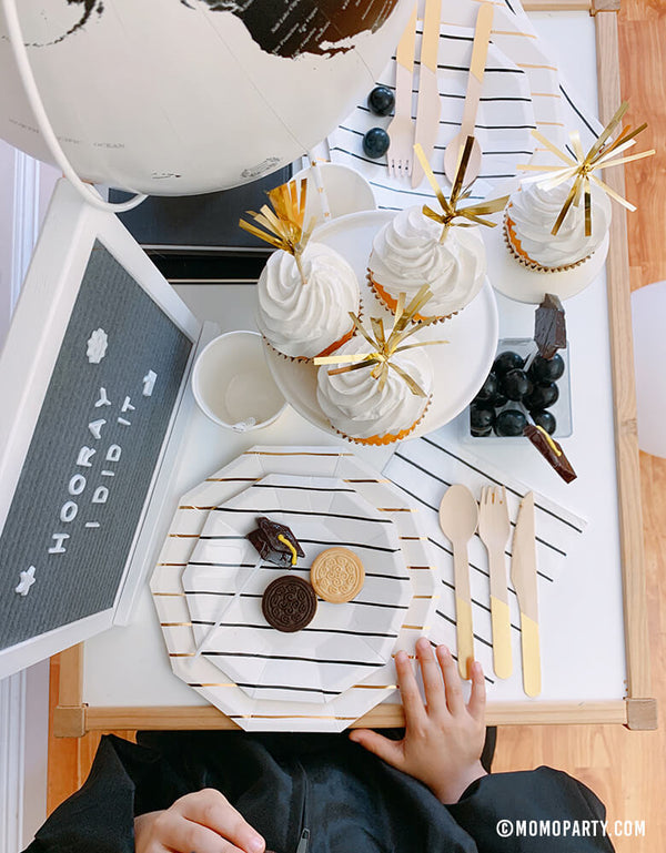 "modern graduation party at home idea with boy wear a black graduation gown siting in front of his table with  black and gold stripe plates, napkins, Assorted Gold Dipped Cups, cupcake, cookies,  b&w globe, letter board with ""hooray i did it"" sign, black gum balls"