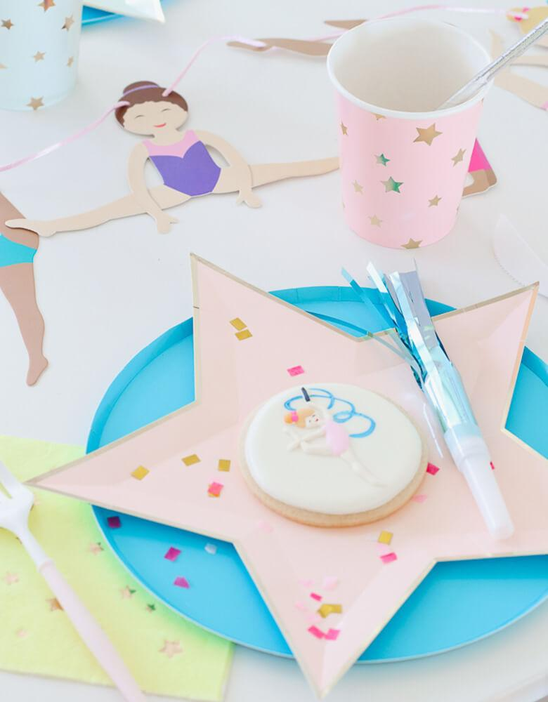 Girl's Gymnastics Themed Party Tablescape with Meri Meri bright die-cut star plates, Oh happy day Blue paper plates, and colorful jazzy star cups, Gymnastic girl cookie, light blue blower