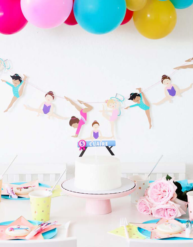 Girl's Gymnastics Themed Party Set with Merrilulu Gymnastics Garland, Ballon garland, Custom Gymnastic Cake topper over a white cake, MeriMeri Star Plates, cups, Oh happy day blue plates,  table and decorations styled by Twinkle Twinkle Little Party