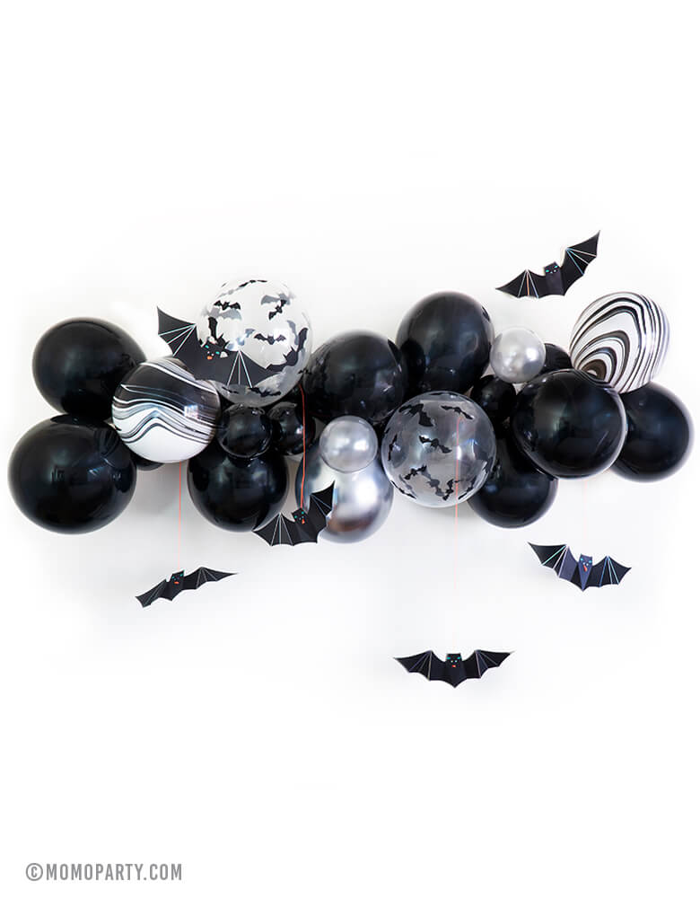 Momo Halloween Bat Balloon Cloud, Balloon Garland with Meri Meri hanging bats decoration. Balloon garland assorted with 11inch and 5inch Halloween-themed latex balloons in black, white, clear bat print, black and white agate, chrome silver and silver, made in USA. Party backdrop, wall decoration for a kid-friendly modern spooky halloween party, Bat party, trick-or-treating halloween party, nightmare before Christmas party, witch themed party, Halloween birthday party and all halloween related celebrations
