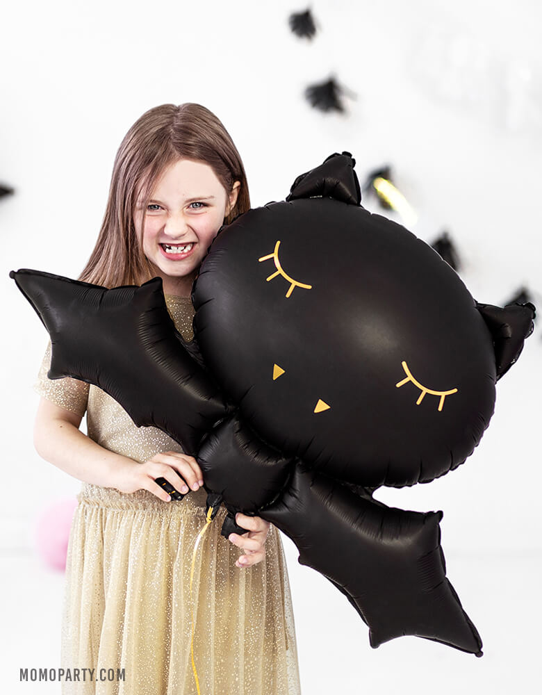 Girl holding a Party Deco 32 inches Halloween Black Bat Foil Mylar Balloon, with gold print on the black bat shape. for a kids modern spooky halloween birthday party. this balloon also perfect for hocus pocus party trick-or-treating party, nightmare before christmas party, witch themed party and all halloween related celebrations
