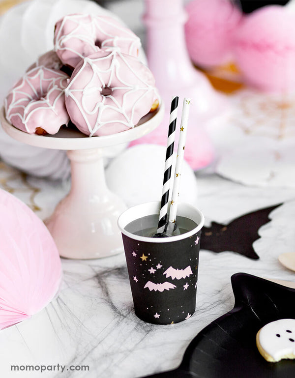 Party Deco Halloween Boo! Paper Cups, with a pastel pink bats and stars in a black cup with Black stripe and Gold star party straws, with a pink spider donuts in a cup stand for a pink Halloween party!