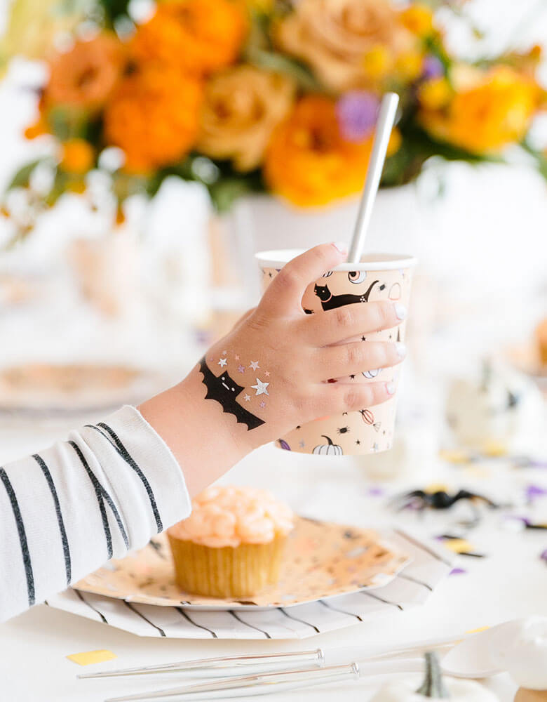 A boy in a mummy costume with daydream society's hocus pocus temporary tattoos on his hand holding a party cup in a fun kid's Halloween party full of pretty fall flower arrangment and delicious treats