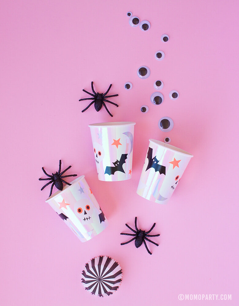 Meri Meri_Halloween-Icons-Cups on the pink background with spider and goggle eyes decorations around