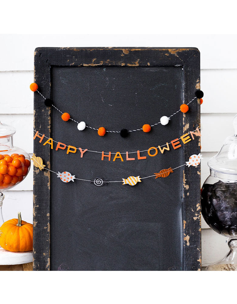 A My Mind's Eye Halloween Mini Banner Set featuring trick or treat candies and mini pom poms and spelled word of Halloween hung on a black sign with pumpkins and halloween candy jars on the table