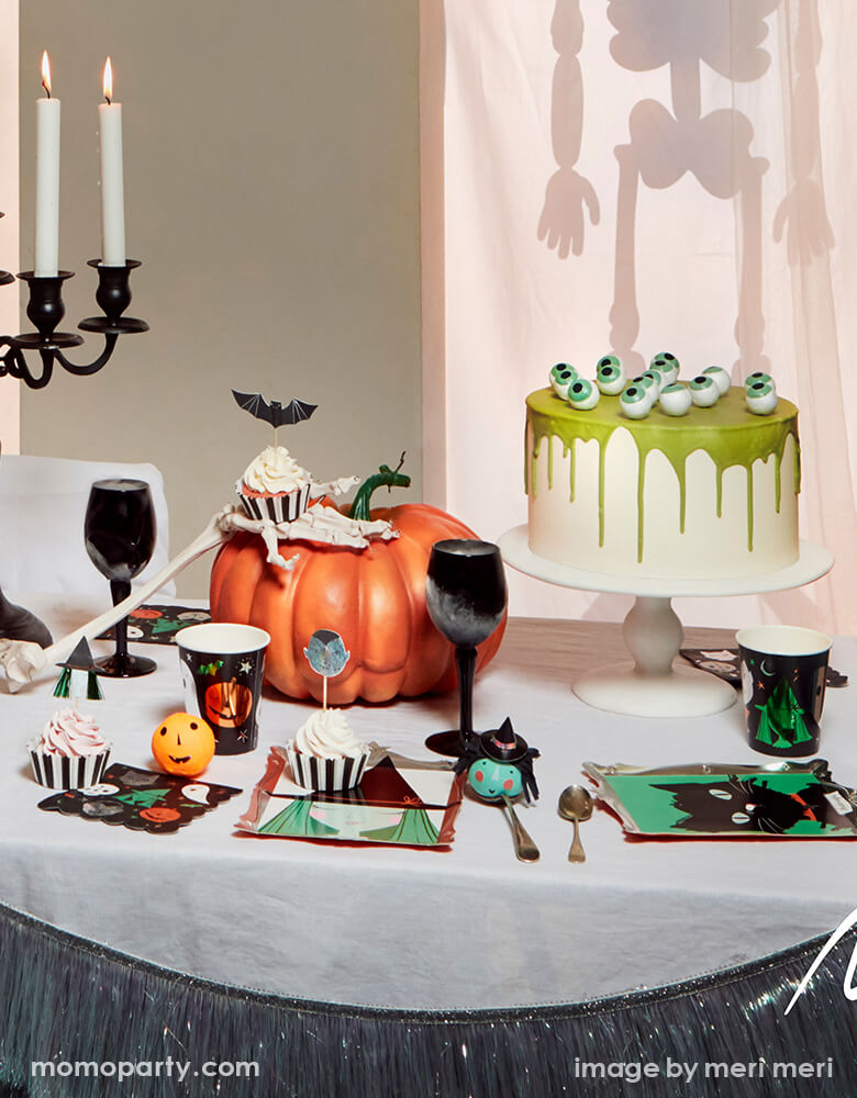 Halloween party table with Meri Meri Halloween Motif Frame Plates of Luna witch, Midnight the black cat, Halloween Motif cups, cupcakes with bat, witch, and vampire from Halloween motif cupcake topper kit. cake with eyeballs on it, candles, pumpkin decorations, and Silver Tinsel Fringe Garland decorated the front of the table