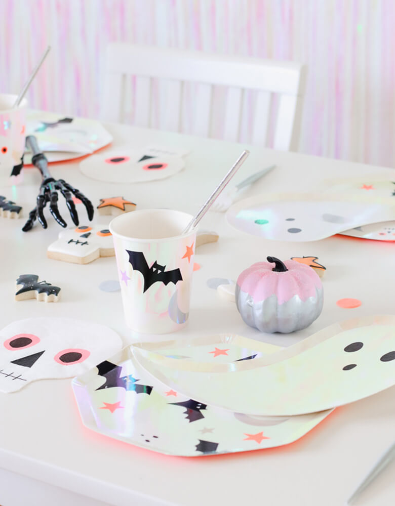 Meri Meri Halloween Iridescent Party Supplies of ghost plates, bat cups, skull napkins on a table of halloween decorations