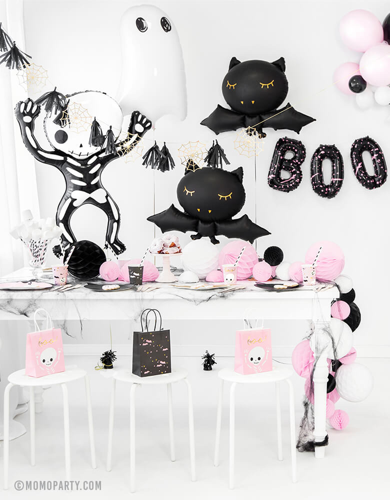 a Pink Halloween party decorated with Party Deco Halloween Skeleton shaped Foil Mylar Balloon, Halloween Ghost Foil Mylar Balloon, Black bat foil balloon, and golden spiderwebs and black tassels garland. BOO Letter Foil Balloon Set. there are pink ghost and black bats gift bags on each chair.  These cute halloween balloons also perfect for Kid-Friendly modern spooky halloween party, trick-or-treating halloween party, nightmare before christmas party, witch themed party and all halloween related celebrations
