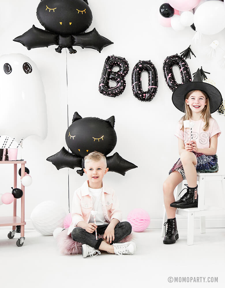 a boy and a girl who wearing witch hat, seating in a room decorated with Party Deco Halloween Skeleton shaped Foil Mylar Balloon, Halloween Ghost Foil Mylar Balloon, Black bat foil balloon, and golden spiderwebs and black tassels garland, celebrating a Pink Halloween. These halloween balloons also perfect for Kid-Friendly modern spooky halloween party, trick-or-treating halloween party, nightmare before christmas party, witch themed party and all halloween related celebrations