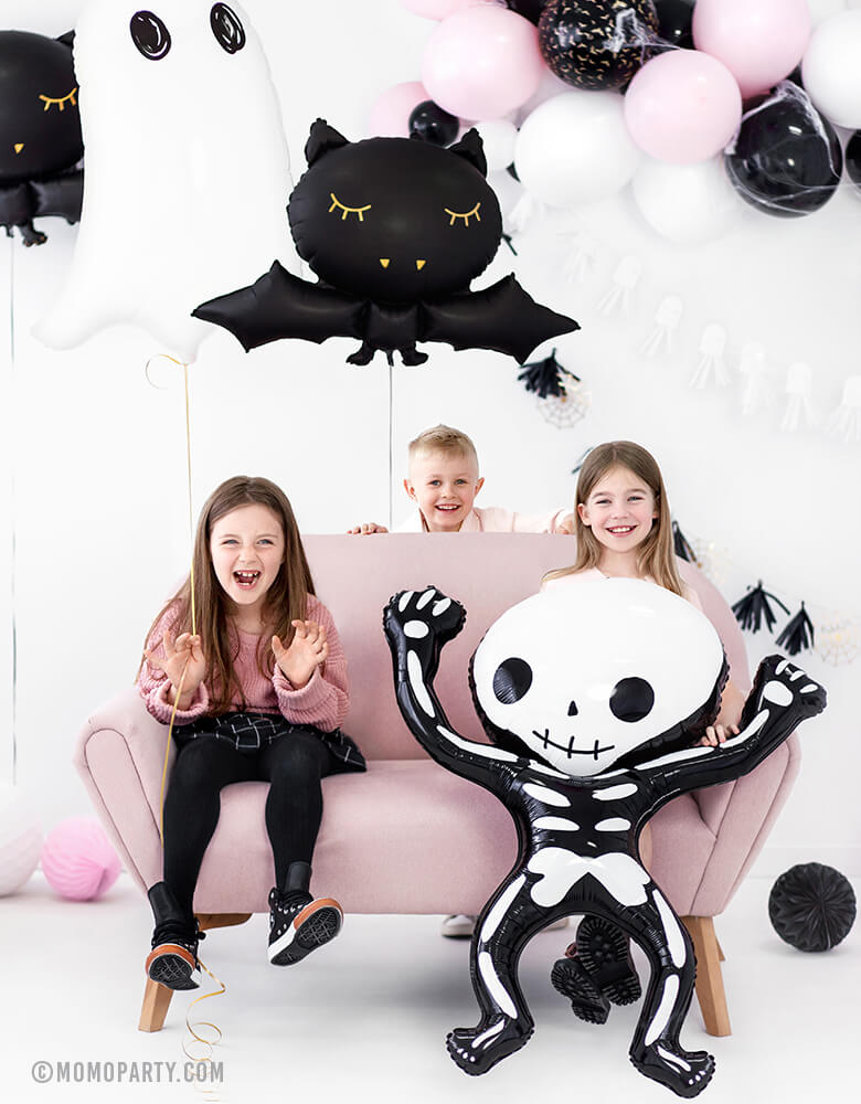 boy and girls seating on the sofa and holding a Party Deco Halloween Skeleton shaped Foil Mylar Balloon, with a Halloween Ghost Foil Mylar Balloon, and Black bat foil balloon, pink white and black mixed balloon garland on the wall, celebrating a Kid-Friendly modern spooky halloween party, trick-or-treating halloween party, nightmare before christmas party, witch themed party and all halloween related celebrations
