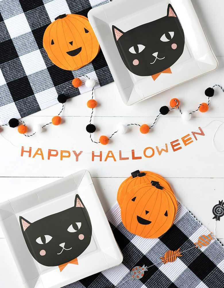 A My Mind's Eye Halloween Mini Banner Set featuring trick or treat candies and mini pom poms and spelled word of Halloween laid on a party table with party plates featuring black cat design and halloween pumpkin napkins