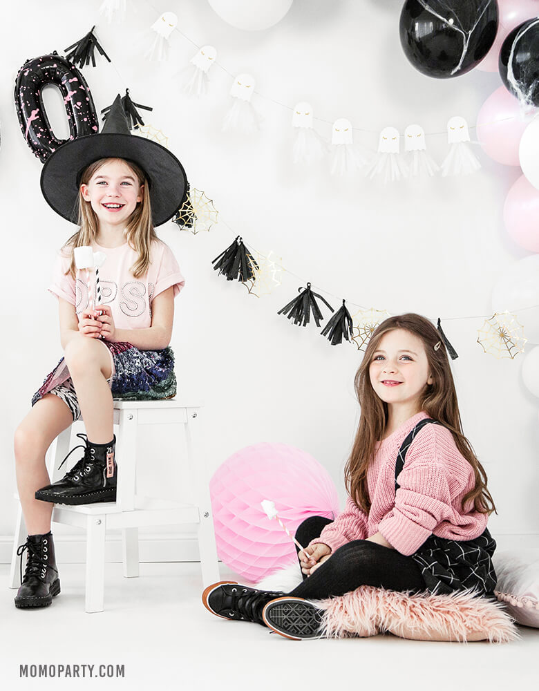 2 girls wearing witch hat, pink sweaters, seating in a room decorated with Party Deco golden spiderwebs and black tassels garland, ghost garland, pastel pink and black balloon garland, celebrating a Pink Halloween party. These cute halloween decorations also perfect for Kids modern spooky halloween party, trick-or-treating halloween party, nightmare before christmas party, witch themed party and all halloween related celebrations