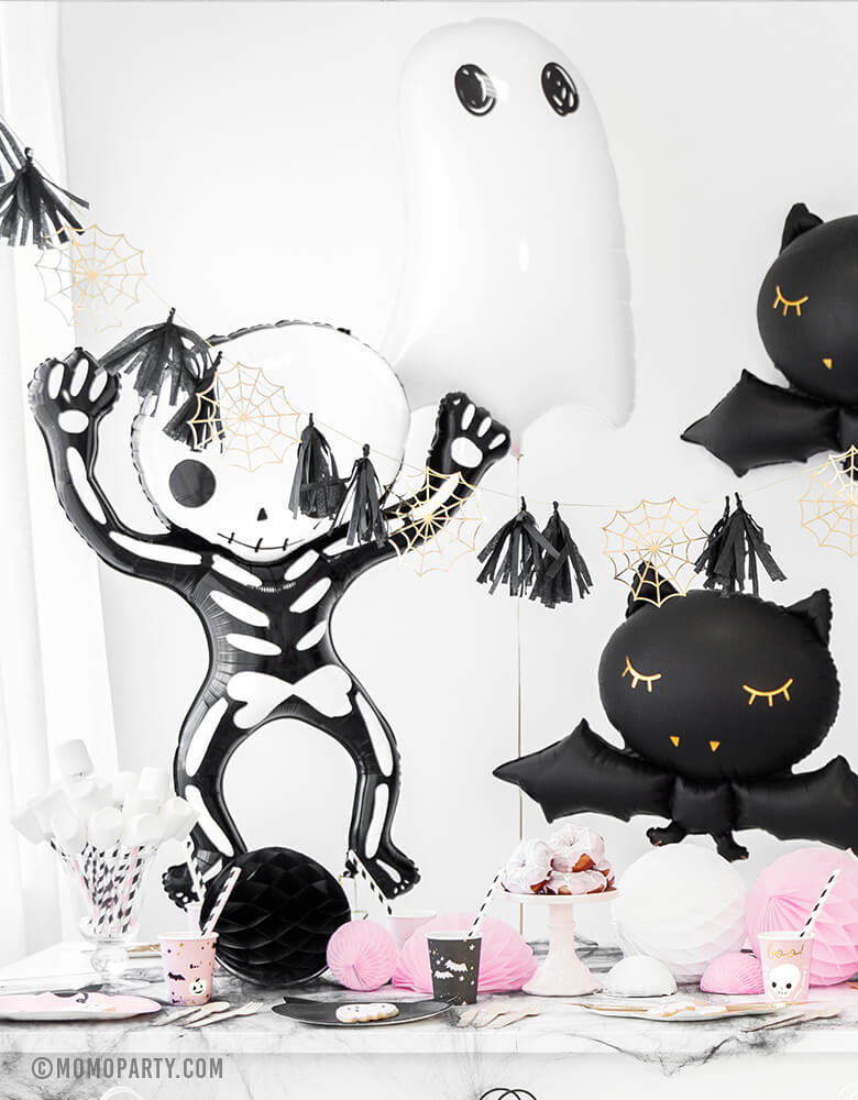 Pastel Pink Halloween party table full of halloween tablewares, decorated with Party Deco Halloween Skeleton shaped Foil Mylar Balloon, Halloween Ghost Foil Mylar Balloon, Black bat foil balloon, and golden spiderwebs and black tassels garland. These halloween balloons also perfect for Kid-Friendly modern spooky halloween party, hocus pocus party trick-or-treating party, nightmare before christmas party, witch themed party and all halloween related celebrations