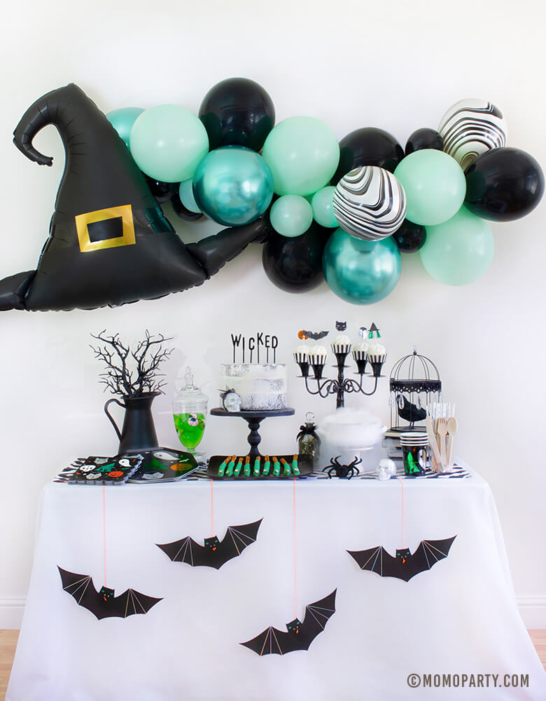 "Momo Party Witch Please themed Halloween Party at home inspiration look with Anagram Witch Hat Satin Foil Balloon and pastel Green toned Latex Balloon Garland as wall decoration backdrop. Table set up with Meri Meri Halloween Motif Dinner Plates, napkins and cups, cake with My minds eye black letter board cake topper spelled of ""Wicked"", witch fingers pretzels, Meri Meri Hanging Bats in front of the table. Inspo for a kid-friendly modern spooky halloween party, nightmare before Christmas party"