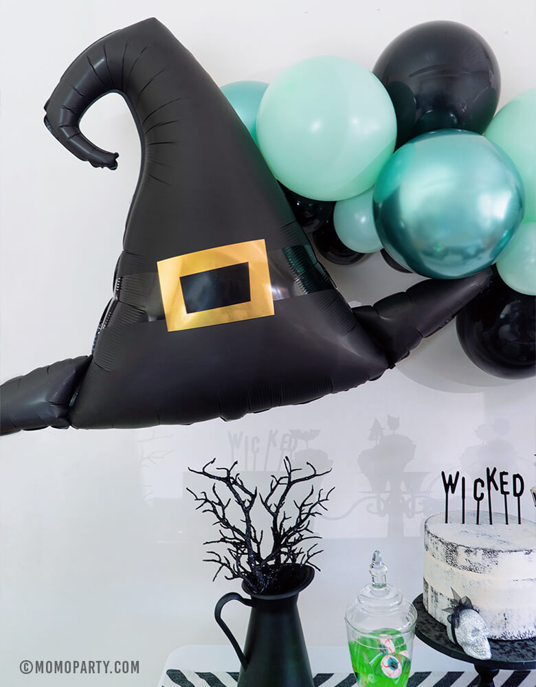 "Close up look of Momo Party Halloween collection, Witch Please Party, Anagram 39"" Halloween Witch Hat Satin Foil Balloon and Pastel Matt Green, Chrome Green, and Black color mixed Latex Balloon Garland as wall decoration, black pot with black branch, white cake with letterboard cake topper spelled ""Wiched"", Apple jelly with eyeball candy in a Jar. Creep cool look for A Modern Witch Inspired Halloween Party"