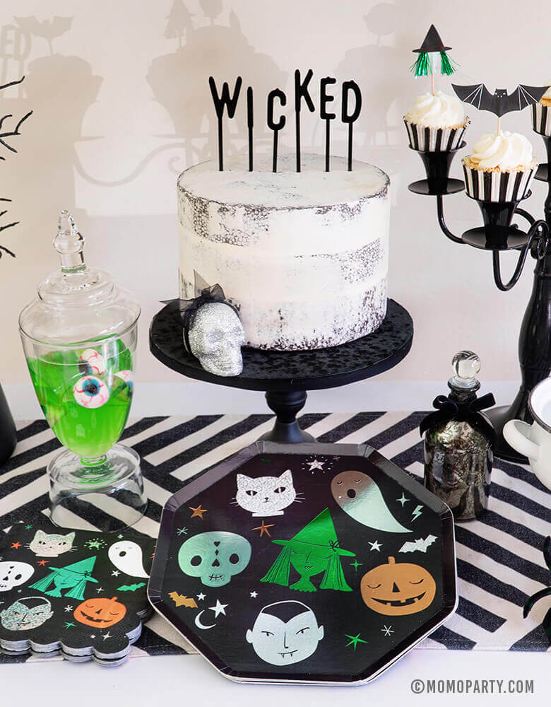 "Close up look of Momo Party Halloween collection, Witch Please Party Dessert Table Set up with Meri Meri Halloween Motif Dinner Plates, napkins, cake with black letter board cake topper spelled of ""Wicked"", Apple jelly in with eyeball candy in a jar, Witch poisons and potions, cupcakes with Meri Meri Halloween Motif Cupcake topper on top of black candle chandelier. for a Creep cool look for A Modern Witch Inspired Halloween Party"