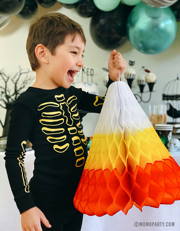 boy wearing skeleton pjs, happily holding a huge paper made candy corn honeycomb decoration in front of a witch themed halloween birthday party with chrome green, black, pastel matt mint color mixed balloon garland. This huge Hand-crafted and hand-dyed Candy Corn in the traditional white, yellow, and orange stripes, unique fun party decoration for sweeten your little one's halloween party!