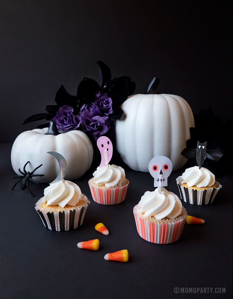 Halloween  skull, ghost, spider, and moon Cupcake toppers on cupcakes, white pumpkin decoration, black purple flowers, candy corns for Momo party kids Halloween decoration idea
