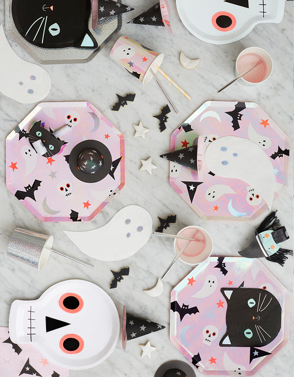 A kid-friendly halloween party table with Meri Meri Halloween iridescent foil Icons Side Plates, Halloween Holographic Ghost Napkins, Black Cat Halloween plates on top of Silver Sparkle Side Plates, Black Cat Halloween Napkins, skull plates, Halloween Icons cups, Silver Sparkle Tumbler Cups, and bats, stars cookies around them, a cute set up for a modern pinky halloween party