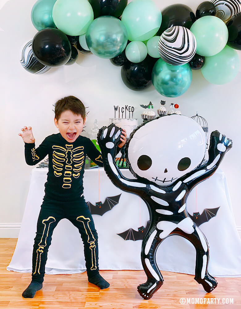 boy dance with Party Deco - Halloween Skeleton Foil Mylar Balloon, The balloon is designed in the shape of a funny skeleton and measures 33 x 39 inches. Add this modern fun skeleton foil balloon to your or your kid-friendly modern spooky halloween party, trick-or-treating halloween party, nightmare before christmas party, witch themed party and all halloween related celebrations