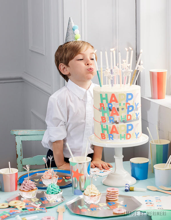 boy blowing candles on his birthday with  Meri Meri Silver Happy Birthday Palette Side Plate with multi-color texts on it on the table