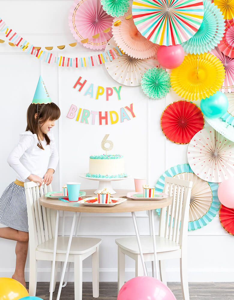 girl's 6 years birthday party table set up with colorful letters Happy Birthday Banner, cake, backdrop decorations