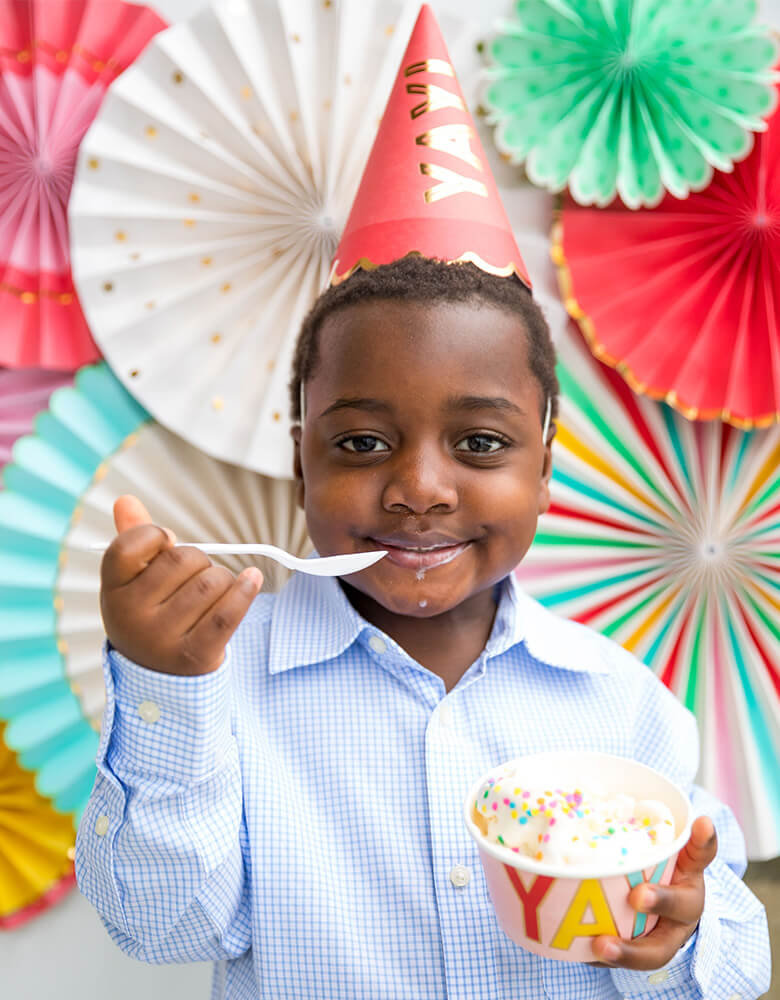Boy wear Hip Hip Hooray Colorful Party Hats eating ice cream