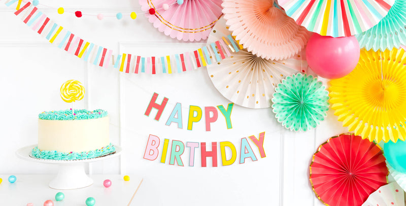 colorful letter happy birthday banner with backdrop paper fans