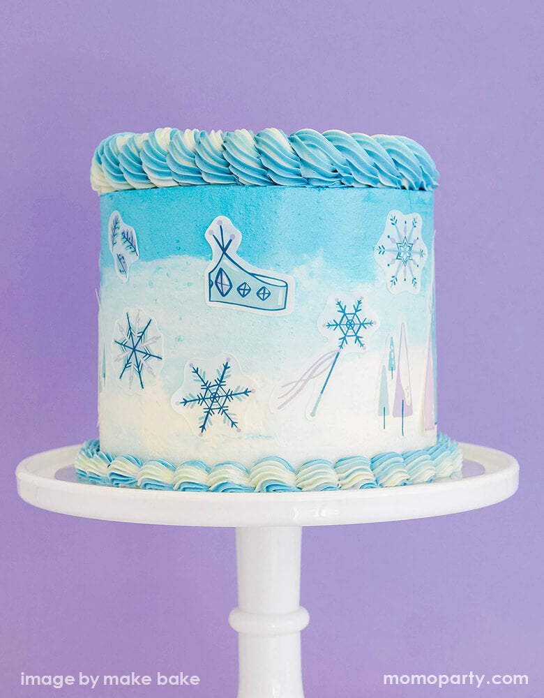 a blue and white buttercream cake on a white cake stand, decorated with Make Bake shop Ice Princess Deluxe Cakescape Edible Stickers with blue ice-y castle, snowflakes, crown and blue trees designs. ready for your little one's Frozen or winter wonderland themed party, Let it snow party