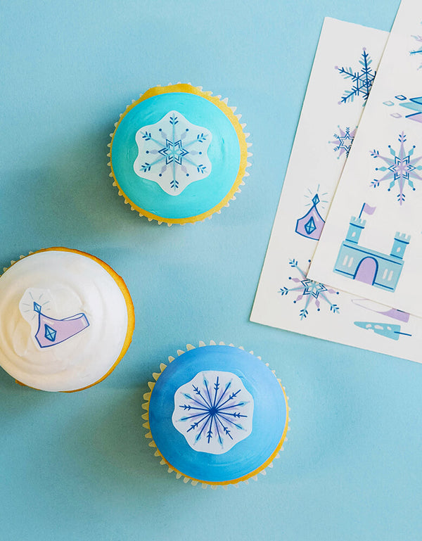 blue and white cupcakes decorated with Make Bake shop - Ice Princess Edible Decorating Stickers, Artwork by lindsey balbierz for Make Bake. these stickers set include 2 sheets/24 edible stickers per pack with blue ice-y castel, snowflakes, crown and blue trees designs, 100% edible and super kid-friendly, Vanilla-flavored. Simply peel it and apply to iced cakes, cupcakes, cookies, These easy baking hacks will be a hit at your little one's Frozen or winter wonderland themed party, Let it snow party