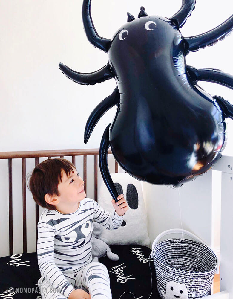 A boy in mummy costume holding a giant Halloween Spider foil Balloon on his bed with Halloween decorations