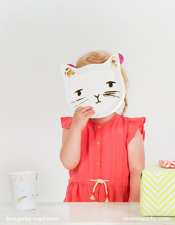 a Girl wearing a red dress, she holds a Meri Meri Cat plate covering her face. This cat paper plates feature an adorable illustrated cat face die cup shape, complete with delicate whiskers picked out in shimmering gold foil. they'll look purrfect on the party table of a Cat themed birthday party, Kitty Cat party, Pet's party, Pet's birthday party, Girl themed birthday party