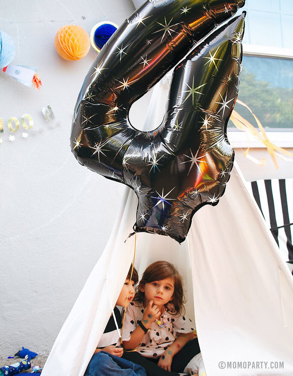 "Boy and Girl at Space Themed Birthday Party holding a 38"" Black Sparkle Jumbo Number Four Foil Mylar Balloon in the teepee for his 4 years birthday"