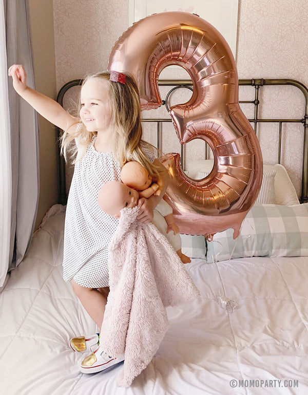 A blond girl holding a baby doll and a Large Rose Gold Number 3 Foil Mylar Balloon standing on her bed looking out window at her 3 years birthday