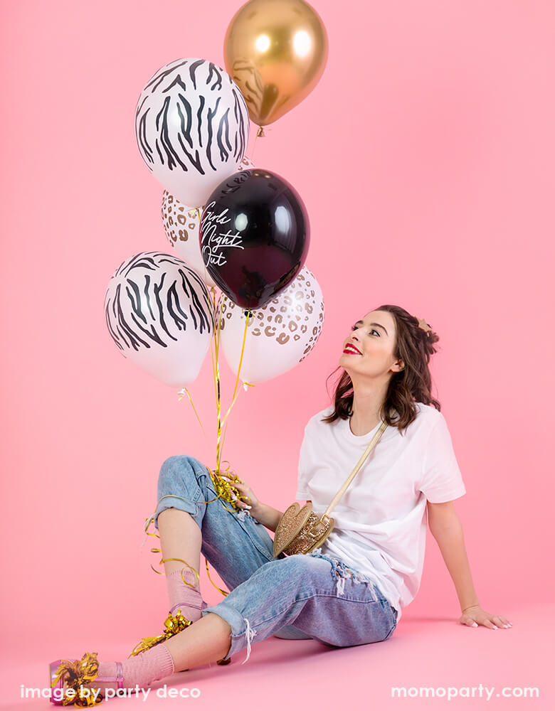 "young lady sitting on a pink background, holding a balloon bouquet of Party Deco Leopard Print Latex Balloon, zebra print latex balloon, gold latex balloon, and black latex with ""girls night out"" text latex balloon"