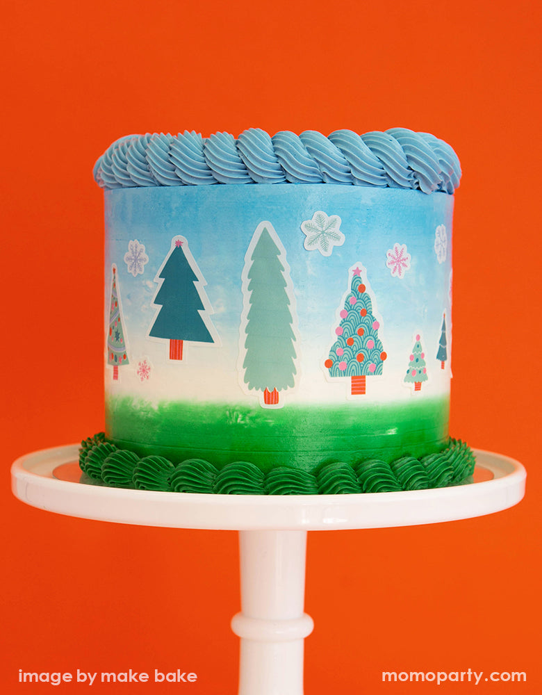 a blue white and green buttercream cake on a white cake stand, decorated with Make Bake shop Let's Get A Tree! Cakescape Edible Stickers with snowflakes and many kinds of trees designs. These easy baking hacks cakescape edible stickers so easy to make decorating holiday cakes so much easier!