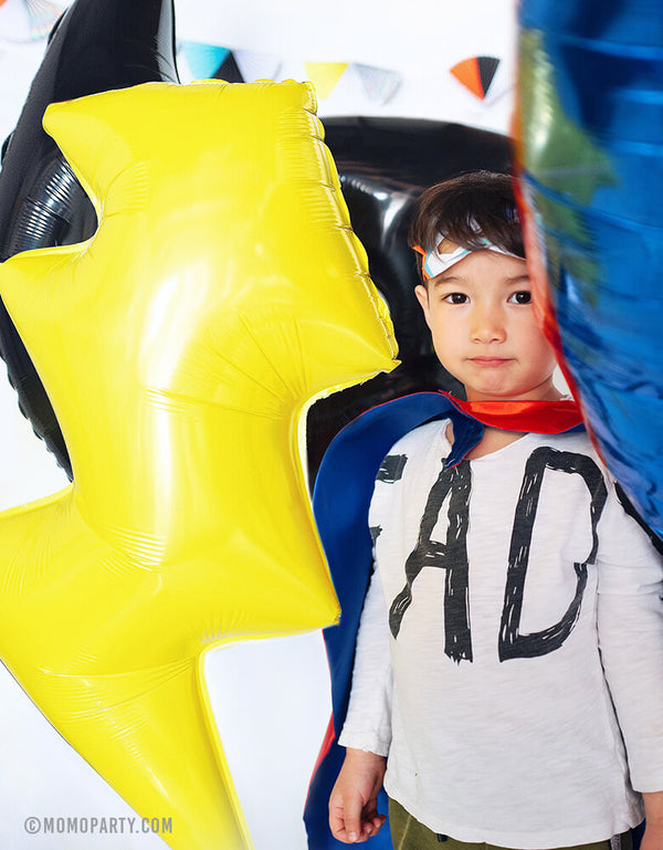 boys standing within Lightning Bolt Foil Balloon, superman emblem balloon, Bat mask Balloons