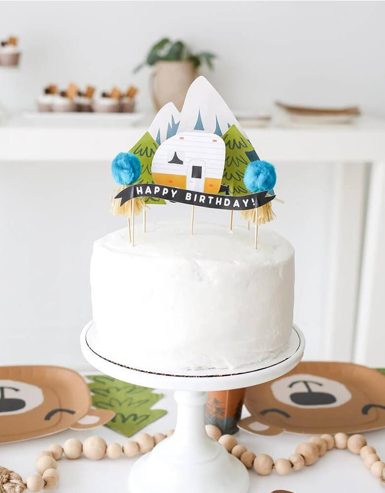 Naked cake with camping themed cake topper set, with happy birthday sign on the snow mountain, camper, trees, and pom poms from Lucy Darling Little Camper Party In A Box Set, for a kid camping themed birthday party