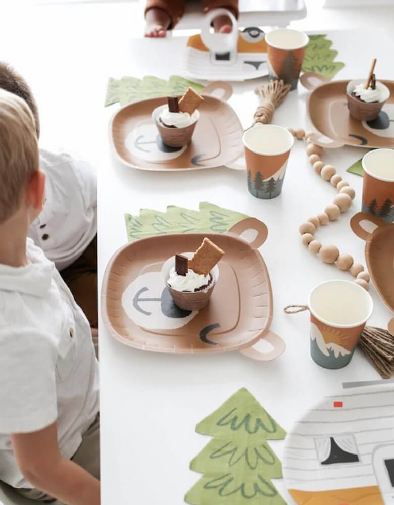 Kids celebrating and sitting around a Camping themed party table. Table set up with cupcakes on a Cute Brown Bear head shaped dinner plates from Lucy Darling Little Camper box set, tree shaped napkins around it, drinks in the mountain patterned paper cups, also camper shaped plates on each side of the table, wood ball chain in the middle of the table as centerpiece.