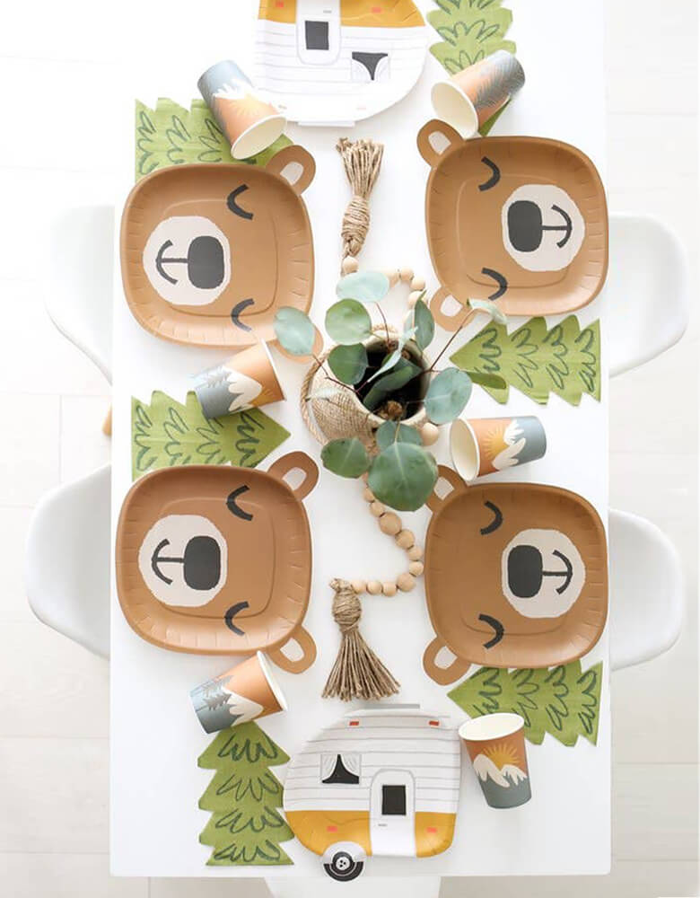 Camping themed party table set up with Lucy Darling Little Camper - Party in a Box. Top view table look with 4 set of Happy Cute Brown Bear head shaped dinner plates and Tree shaped napkins, paper cups in the middle,  2 camper shaped plates on each side of the table, Green plants in the vas and wood ball chain as center piece. A party ready for a camping themed birthday, Lets exploring themed birthday, Woodsy Rustic Wedding Decoration, Baby shower