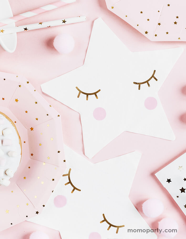 An adorable pastel pink table filled with star-shaped napkins, baby pink plates with star designs and a mix of pink striped straws and gold star straws for a Twinkle Twinkle Little Star themed party